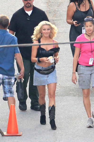 "Julianne Hough shows off one of her ""Rock of Ages"" costumes as she makes her way to the movie set before filming a scene. Hough was showing off her figure in a cut up black top, pink bra, denim skirt, studded cowboy boots and a leather fanny pack."