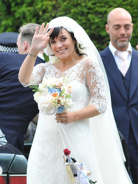 Lily Allen THE HAPPY COUPLE! Lily Allen and Sam Cooper emerge from St James The Great Church in Cranham after their wedding. Lily was wearing a Chanel lace dress created by Karl Lagerfeld and was looking estatically happy following her marriage to Sam.  The singer-turned-businesswoman was carrying a bouquet with a knitted bride and groom hanging from the stems.