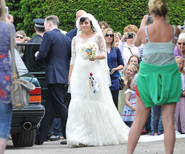 THE HAPPY COUPLE! Lily Allen and Sam Cooper emerge from St James The Great Church in Cranham after their wedding. Lily was wearing a Chanel lace dress created by Karl Lagerfeld and was looking estatically happy following her marriage to Sam.  The singer-turned-businesswoman was carrying a bouquet with a knitted bride and groom hanging from the stems.