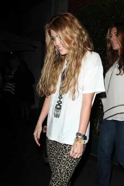 Miley Cyrus Miley Cyrus, wearing a Native American inspired outfit, leaves Mr. Chow restaurant in Beverly Hills after grabbing dinner with a couple of friends. Miley could be seen wearing leopard print leggings, a long turquoise and silver necklace and feather earrings.