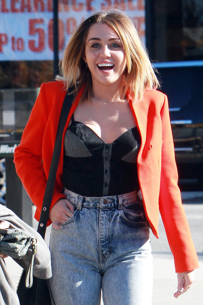 Miley Cyrus Miley Cyrus shows off her new haircut in a pair of high waisted jeans and a red blazer while out for lunch with a friend. The Disney star, who is reportedly dating actor Liam Hemsworth, looked upbeat as she rocked a pair of round sunglasses on her way to the car.