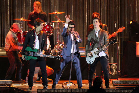 Jonas Brothers **VIDEO AVAUILABLE** Nick (military jacket), Joe (suit and glasses) and Kevin Jonas film a late night concert on an LA beach for their TV show
