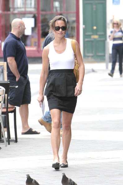 Pippa Middleton steps out for a lunchtime stroll in the warm London weather near her office in Kensington. Pippa was in a simple monochrome skirt and vest accessorised with a mustard handbag.