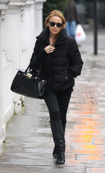 Kylie Minogue strutts out of her Chelsea home wearing an all black ensemble.