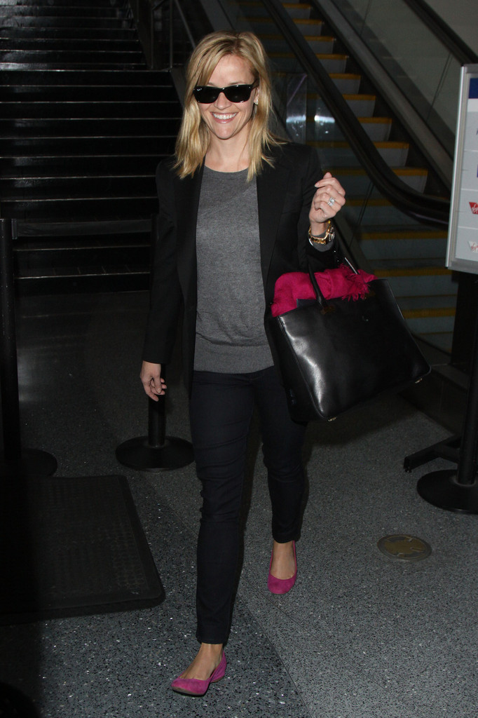 Reese Witherspoon is all smiles as she heads out of LAX after landing in Los Angeles.