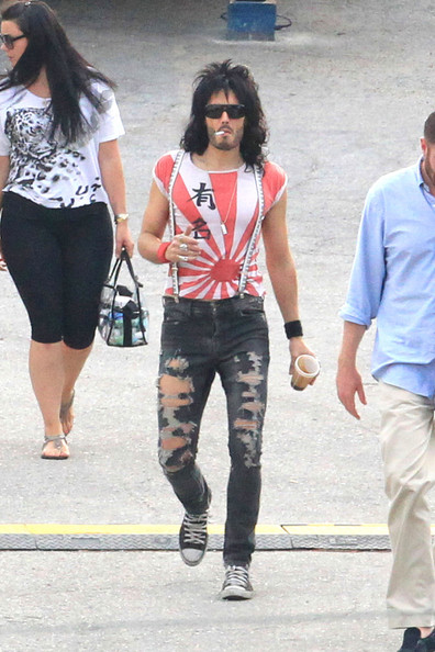 "Russell Brand sports two different costumes as he is spotted on the Miami set of the upcoming film ""Rock of Ages"". Brand was first seen wearing a Japanese inspired t-shirt, piano keys suspenders and ripped up jeans as he smoked a cigarette and drank coffee while leaving his trailer. Brand then showed off his hip tattoo in a burgundy shirt, star suspenders and low rise black jeans."
