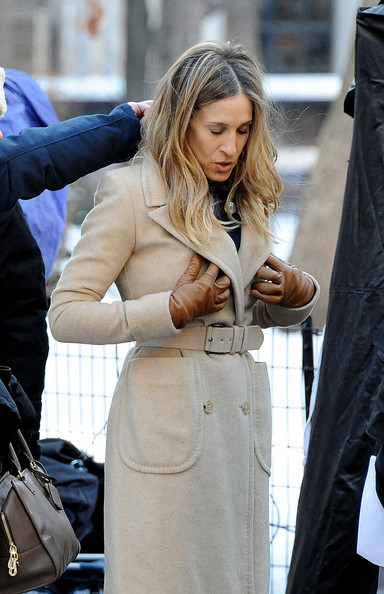 "Sarah Jessica Parker, holding onto a large pretzel, films a scene with Pierce Brosnan on the set of ""I Don't Know How She Does It"" in NYC. The co-stars filmed on location in Madison Square Park, bundled up for the snow."