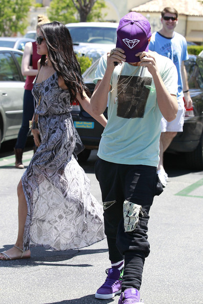 Justin Bieber and girlfriend Selena Gomez return to Bieber's customized Mercedes-Benz van after a romantic movie date in Los Angeles. Bieber, wearing a James Dean shirt and dollar bill embroidered shorts, looked a little shy coming out of the theater as he covered his face with his purple baseball hat. Selena, wearing a flowing, summery dress, managed to drop and temporarily lose her cell phone in the parking lot but quickly recovered it with some help.