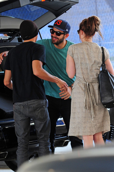 Una morena Dakota Johnson espera con Jordan Masterson para su hermano Jesse Johnson obtenerlos de LAX.  Dakota y Jesse, que son medio hermanos, son dos de los hijos de Don Johnson.