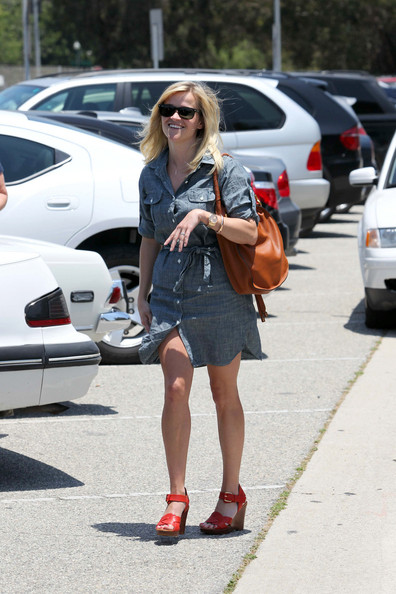 An upbeat Reese Witherspoon shows off her wedding band as she leaves Byron